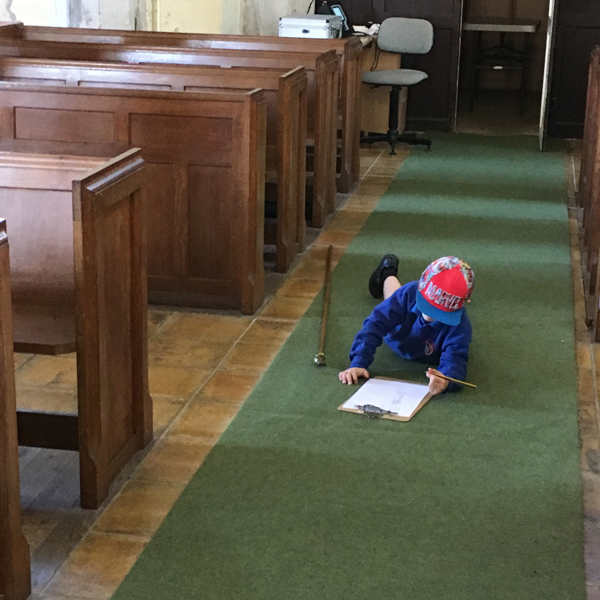 Child laying is the church aisle drawing