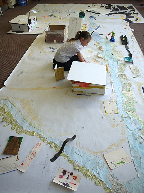Child working on a huge map spread out on the ground