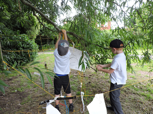 Two boys building teh haunted house in a tree from the ground