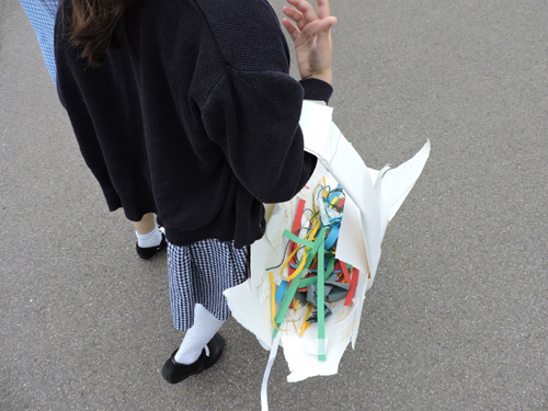 Girl carrying a basket made from paper called carrying back the basket