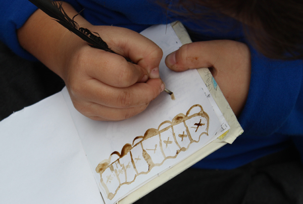 Close up of a child drawing with the home made ink with a feather made into a quill