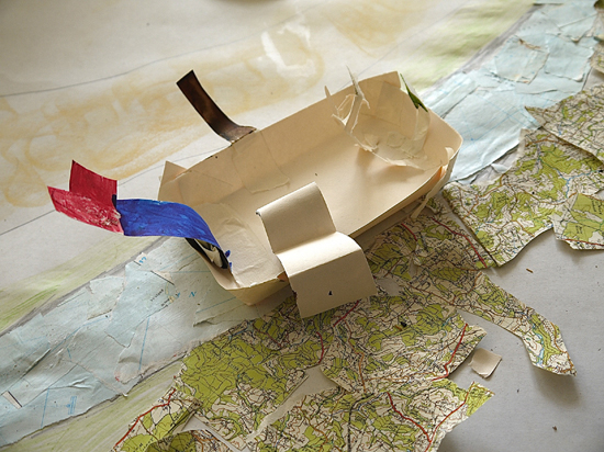 Image of a small boat setting sail on the fantastical map